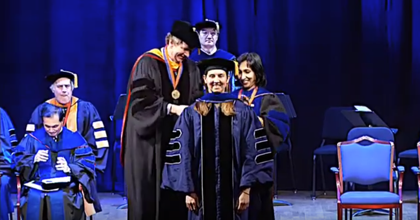 A student receives their doctoral hood from Dean Riffat and Dr. Plesniak