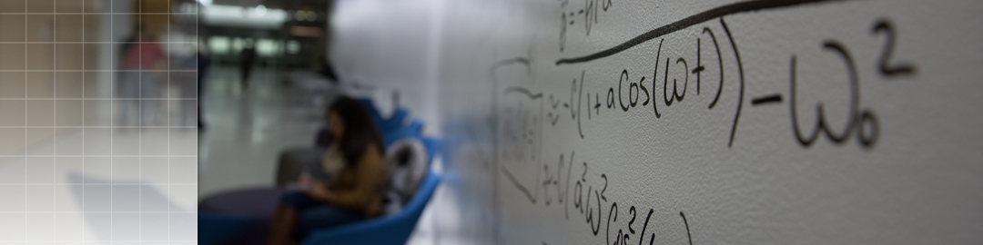 photo of an equation written on the dry erase wall with a student studying in the background