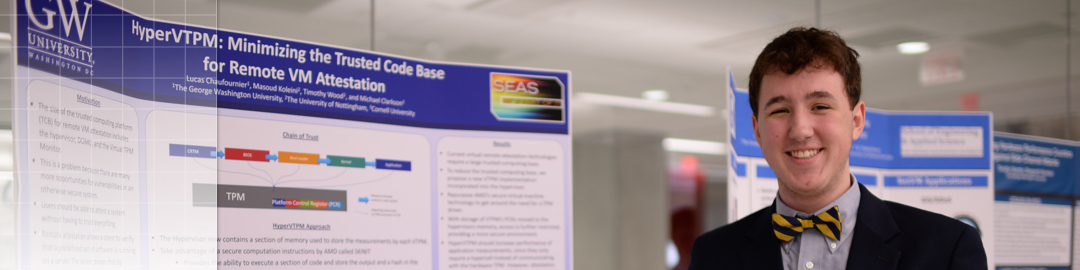 Photo of a male student in front of a research poster