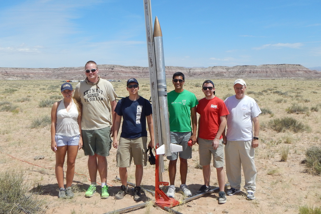 photo of 6 students in front of a small rocket